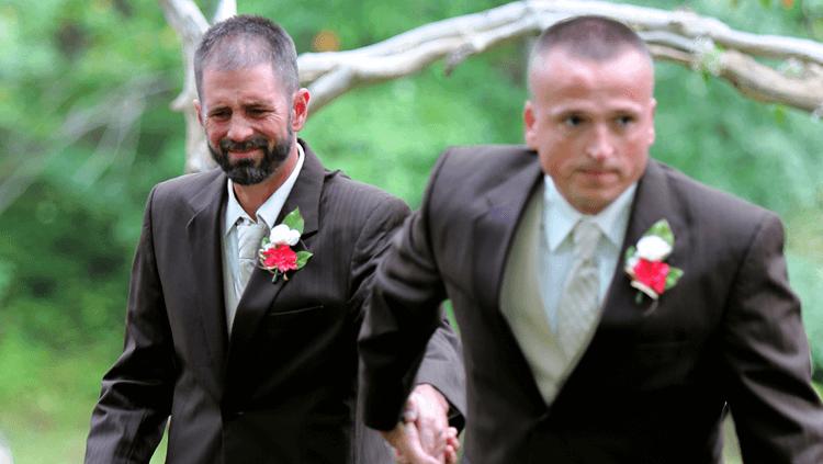 känslomässigt bröllopsfoto av pappa och styvpappa
